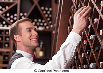 Handsome young worker is choosing an elegant drink -...