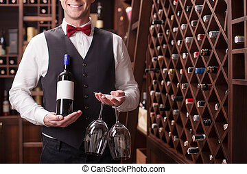 Skillful young sommelier is serving a customer - Experienced...