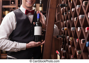 Cheerful male waiter is working in winehouse - Professional...