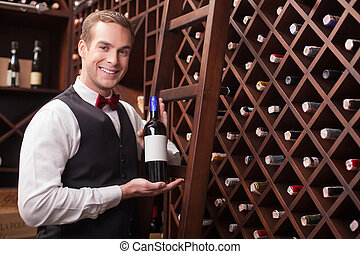 Attractive young sommelier is showing elegant drink -...