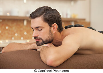 Attractive young guy is relaxing at beauty salon - Handsome...