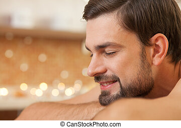 Attractive young guy is resting at spa - Close up of...