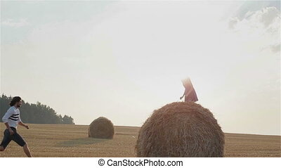 Young couple climbing over haystack - Romantic couple...