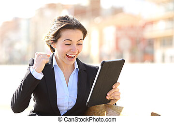 Euphoric successful executive watching a tablet sitting in a...