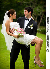 Couple Getting Married - An attractive young groom carrying...