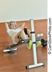 Elderly woman exercising in gym