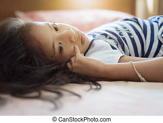 Cute girl lie down on the bed under warm light