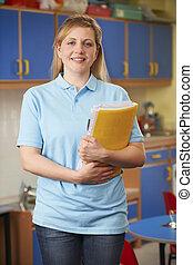 Childcare Worker Standing In Nursery