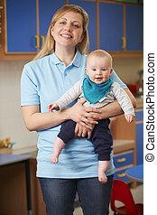 Portrait Of Nursery Worker Holding Baby