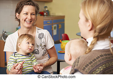 Two Mothers With Chidren Chatting At Playgroup