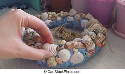 Bonding seashells on decorative wreath. Hand made