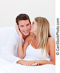 Intimate woman kissing her husband sitting on bed at home