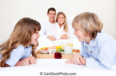Cheerful family having breakfast sitting on bed at home