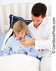 Handsome father checking his son\'s temperature in the...