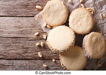 Tasty cookies with cream on paper. Horizontal top view -...