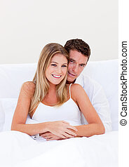 Portrait of an enamored couple sitting on bed at home