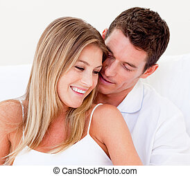 Enamoured couple sitting on the bed at home