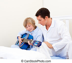 Adorable little boy playing guitar with his father