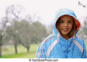 Young cute girl in the rain with blue rain coat. - Young...