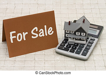 For Sale, A gray house, brown card and calculator on stone background