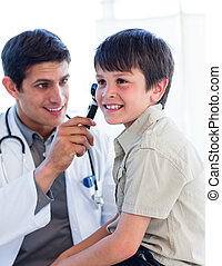 Handsome doctor examining little boy\'s ears at the practice