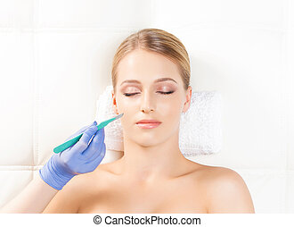 Face with a scalpel. Aging, plastic surgery, and skin rejuvenation concept.