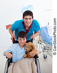 Portrait of a little boy sitting on wheelchair and a doctor...