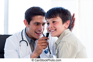 Smiling doctor examining little boy\'s ears at the practice