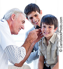 Charming male doctor examining patients ears in the hospital...
