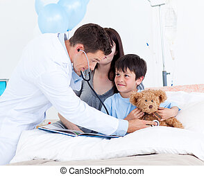 Attentive doctor playing with a little boy and his mother