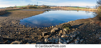 drained pond in winter against blue sky, rural scene,...