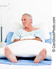 Portrait of a senior man at the hospital lying on bed