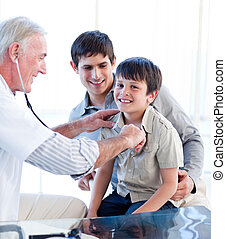 Mature doctor examining a little boy with his father