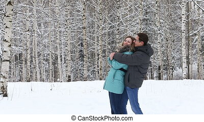 Happy young couple walking in a winter park.