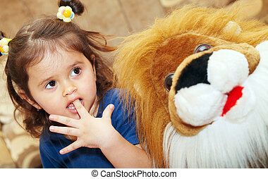 Little girl and teddy lion - Little girl sitting next to a...