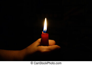 burning candle in the hands of women