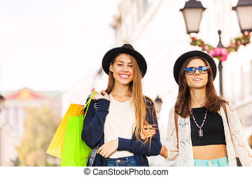 Two happy young women walking with shopping bags on the...