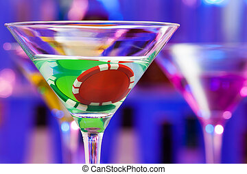 Two casino chips in the bar cocktail glass