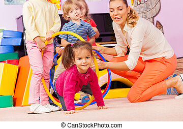 Kids with girl and teacher play active game - Little girl...