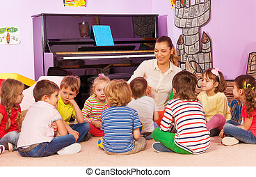 Group of kids sit and listen to teacher tell story - Group...