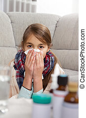 Little girl  sneezing In to tissue