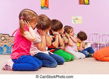 Group of kids in kindergarten pretend to sleep