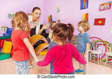 Many kids clap hands with teacher in kindergarten