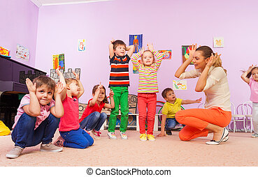 Kids repeat after teacher making ears with hands - Group of...