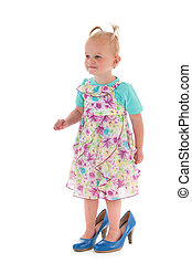 Toddler girl in mothers big shoes - Toddler girl standing...