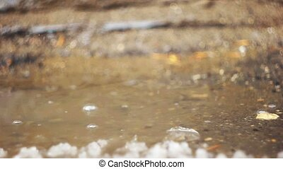 Thawing weather, puddle with splashing water drops