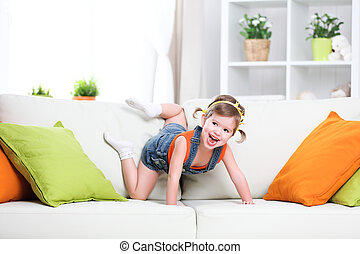 happy child girl playing on couch at home - happy funny...