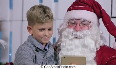 Little Boy Sits in Santa's Lap, Flipping Through pages on Tablet