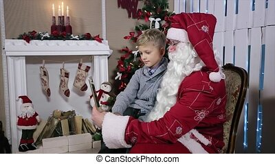 Little Boy Chooses a Gift from Santa on Tablets