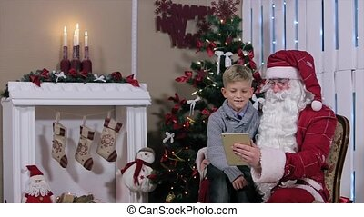 Little Boy Chooses a Gift from Santa on Tablet in Hand